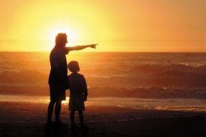 a father showing something to his son at sunset on a beach