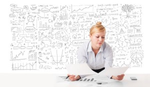 Pretty young businesswoman planning and calculating various business ideas